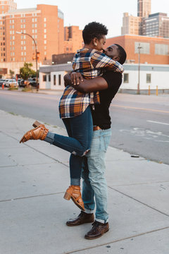 A young black couple walking around the city at sunset