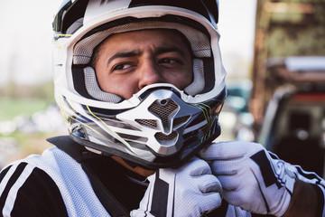 Motocross driver strapping helmet