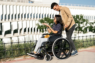 Young woman sitting on a wheelchair and her boyfriend walking
