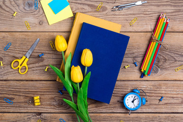 Festive educational background with books, school supplies and tulip flowers on rustic wooden...
