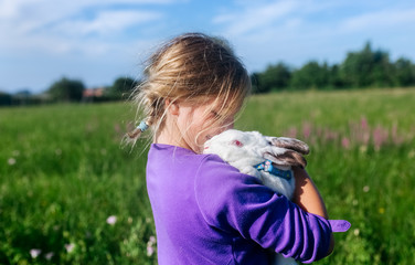 Little girl with a white bunny outdoors