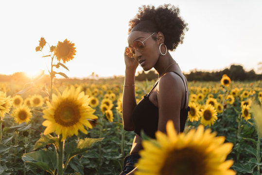A young african american woman in a sunflower field at sunset
