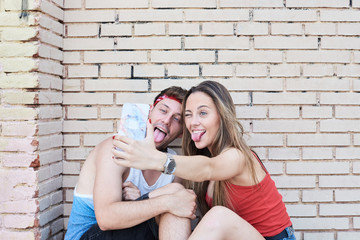 Couple of friends having fun taking selfies against brick wall.