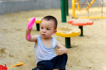 Asian kid in sandpit