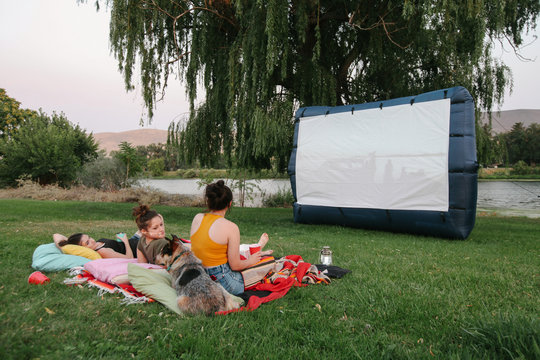 friends and family enjoy watching outdoor movie in yard