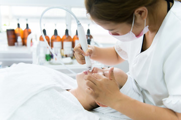 Woman receiving facial treatment in spa