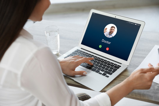 Woman receiving video call from doctor at table in office, closeup. Online chat