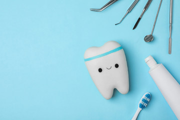 Flat lay composition with dentist tools and tooth on color background. Space for text