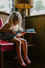 Young Girl Concentrating on Playing guitar