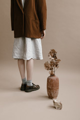 natural still life of person standing, vase of dried leaves and rock on photo studio backdrop