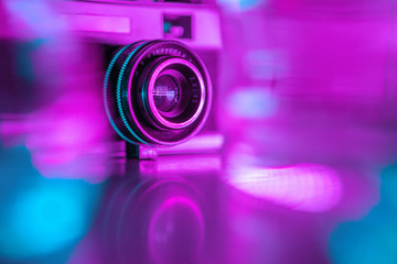 Old retro camera under colorful neon lights