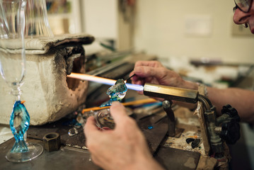 Man in the workshop makes products from glass
