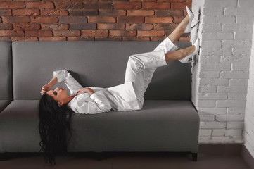 business girl with black hair in a white suit;  in a suit without a bra;  posing in the interior; beautiful girl in white business clothes;