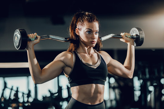 Attractive Caucasian female bodybuilder with ponytail lifting barbell while standing in gym. Train hard and do your best.
