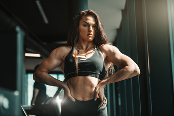 Portrait of beautiful Caucasian female bodybuilder posing with hands on hips in gym. Motivation is right inside you.