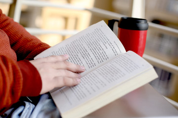 Portrait of man is reading book with water bottle on the table.
