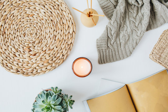 Boho style modern minimal home workspace desk with notebook, succulent, knitted plaid, candle, aroma sticks, straw wicker napkins on white background. Flat lay, top view lifestyle blog concept.