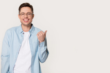 Smiling man in glasses point with finger on copy space