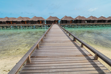 Amazing island in the Maldives ,water villa ,wooden bridge and  beautiful  turquoise waters with  blue sky  background for holiday vacation .