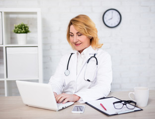 cheerful mature woman doctor or nurse working with laptop in office