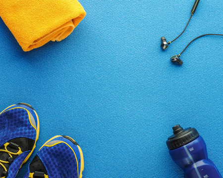Sports equipment flat lay composition, running shoes, yellow towel, smartphone, earphones, fitness tracker and bottle of water on blue background. Concept healthy lifestyle, sport and diet.