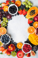 Wall Mural - Frame made of healthy raw fruits, mango papaya strawberries oranges passion fruits berries on oval serving plate on light concrete background, top view, copy space, selective focus