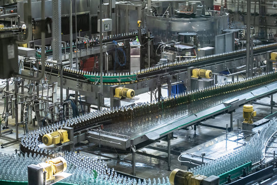 Beer bottles moving on automated conveyor line or belt. Industrial brewery and alcohol production equipment