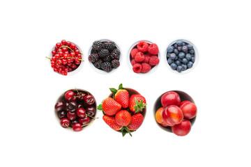 Wall Mural - Top view of mixed berries in bowls, strawberries blackberries blueberries plums red currants raspberries cherries, flat lay, isolated, copy space, selective focus