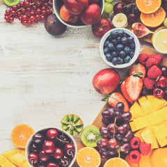 Wall Mural - Healthy raw fruits background, cut mango papaya, strawberries raspberries oranges plums apples kiwis grapes blueberries cherries, on white table, copy space, top view, toned, selective focus