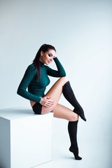 Studio shot of provocative sexy long legged young female model wearing shorts and knee socks