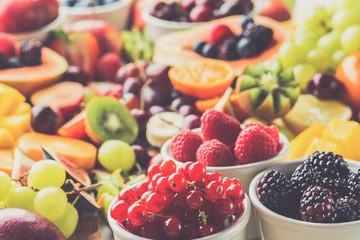 Wall Mural - Healthy cut fruit platter background, strawberries raspberries oranges plums apples kiwis grapes red currants blueberries mango persimmon, toned, selective focus