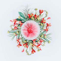 Wall Mural - Round circle composing of tropical leaves and exotic flowers with  paper party fan on white background, top view. Copy space. Floral layout