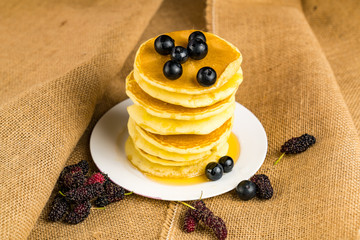 Fototapete - Pile of homemade pancake topped with frshed honey and blueberry in a white plate