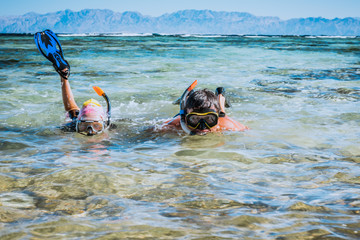 Father and daughter in Red sea with snorkles. Tropical resort, Egypt