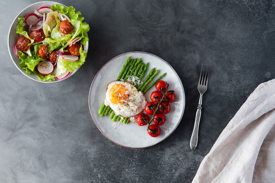Blanched asparagus, fried egg, tomatoes and sald on the bowl, top view. Breakfast concept
