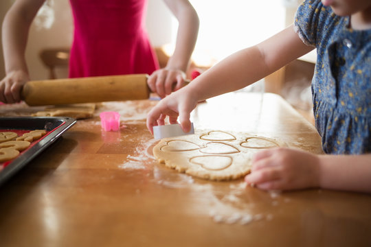 children in the kitchen make homemade cookies. kid cook at home. girl cuts hearts with a cutter