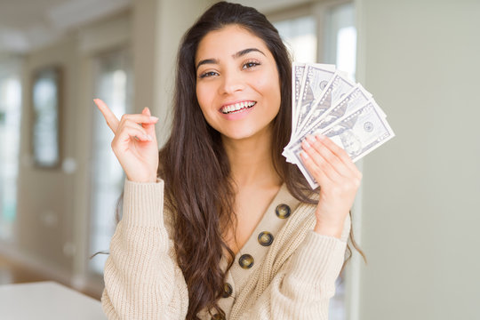 Young woman holding 50 dollars bank notes very happy pointing with hand and finger to the side