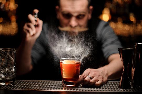 Brutal bartender pours an alcohol cocktail using sprayer