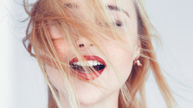 Young blonde woman portrait. Hair blowing in wind. Eyes closed mouth open. Freedom solitude relaxation emotions.