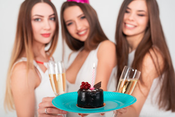 Three beautiful elegant women celebrate holiday party, having fun with cake and drinking cocktails and champagne.