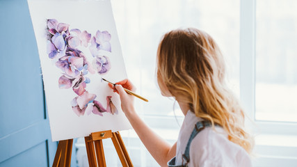 Artist lifestyle. Painting hobby. Imagination and inspiration. Talented woman creating beautiful watercolor floral design. Wall mural