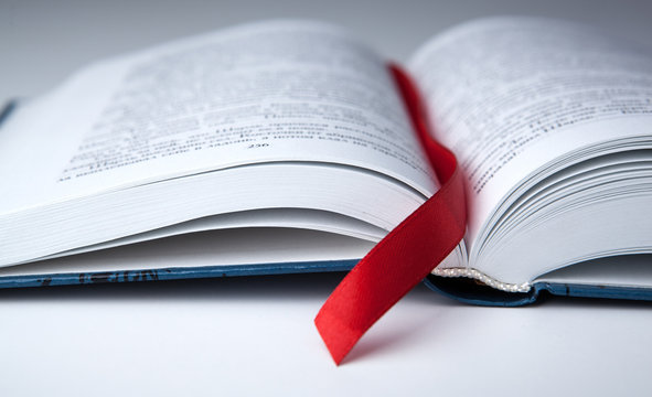 new open book on a gray table with a red ribbon bookmark