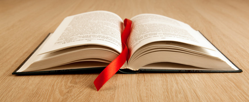 new open book on a wooden table with a red ribbon bookmark