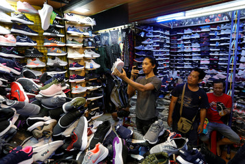 A man takes pictures of a shoe at a market in Jakarta