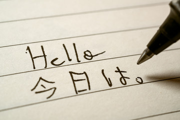Beginner Japanese language learner writing Hello word in Japanese kanji characters on a notebook
