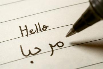 Beginner Arabic language learner writing Hello word in abjad Arabic alphabet on a notebook