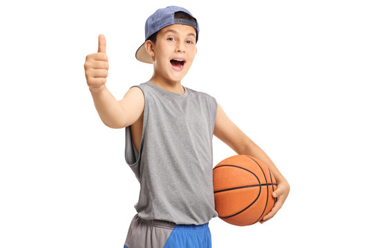 Cool teenage boy with a basketball showing thumbs up