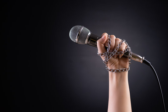 Woman hand with microphone tied with a chain, depicting the idea of freedom of the press or freedom of expression on dark background. World press freedom day concept.