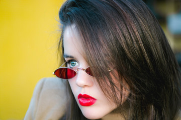 Girl with blue eyes and red lips wearing 80s glasses.