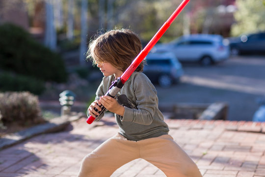 5 year old boy playing with a light saber outside